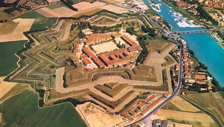 La fortezza si trova a nord-ovest della città di Alessandria ed è da essa separata dal fiume Tanaro. E' la zona più bassa della Regione Piemonte a circa 90 metri sul livello del mare. L'area di Alessandria e' sempre stata destinata ad essere una terra di confine. E' servita come fortezza nel Medioevo e, in particolare, nei secoli XVIII - XX tra i Savoia, la Repubblica di Genova e Milano. La Cittadella è stata costruita sulle rovine del preesistente quartiere di Borgoglio (o Bergoglio), dopo il trattato di Utrecht del 1713, quando Alessandria passò dal dominio spagnolo a quello di Casa Savoia. Per cui, al fine di soddisfare le esigenze di difesa del nuovo stato sabaudo, la fortezza militare fu interamente costruita a scapito dell'antico quartiere provocando una decisa rivoluzione urbanistica della città di Alessandria. La cittadella fu voluta da Vittorio Amedeo II e progettata dall'ingegnere Ignazio Bertola. Nasce così un'immensa fortezza esagonale che si estende su 20 ettari il cui lato più lungo è parallelo alla asse del fiume. La forma esagonale è dovuta alla necessità di difendere il confine lungo della città. La Cittadella è un perfetto esempio di moderna fortezza, si compone di sei bastioni ed e' circondata da fossati che in passato venivano inondati dalle acque del fiume. Vi si accedeva da un lungo ponte di pietra che conduceva ad una grande area circondata da edifici a più piani disposti secondo l'asse dell'antico quartiere di Borgoglio, tutti coperti da resistenti terrapieni costruiti tra il 1749 e il 1831. La costruzione e lo stato di conservazione degli edifici napoleonici sono unici. Durante l'occupazione francese la posizione e l'efficacia delle moderne fortificazioni ha fatto della Cittadella una delle fortezze più spettacolari dell'impero e il più ricco arsenale di tutta Europa. Dopo la Restaurazione il ripristino delle antiche mura dello stato sabaudo ha dato ancora una volta un ruolo fondamentale alla Cittadella. A causa della guerra tra lo stato sab