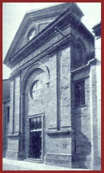 """Esisteva già nel 1486 presso un'ampia casa porticata che giungeva fino a Via Dante, donde l'appellativo """"Domus Magnae"""". Nel 1606 fu aggregata all'Arciconfraternita Romana del Gonfalone e al principio del Settecento fu officiata dai Minori Osservanti, tra il 1765 e il 1769 fu riedificata e nel 1933 restaurata e assunta a sede della Confraternita della SS. Trinità, annessa alla casa di riposo """"Teresio Borsalino"""". Più tardi abbandonata, nel 1977 venne degradata a rimessa per la Questura. Dal 1992 appartiene al Comune."""