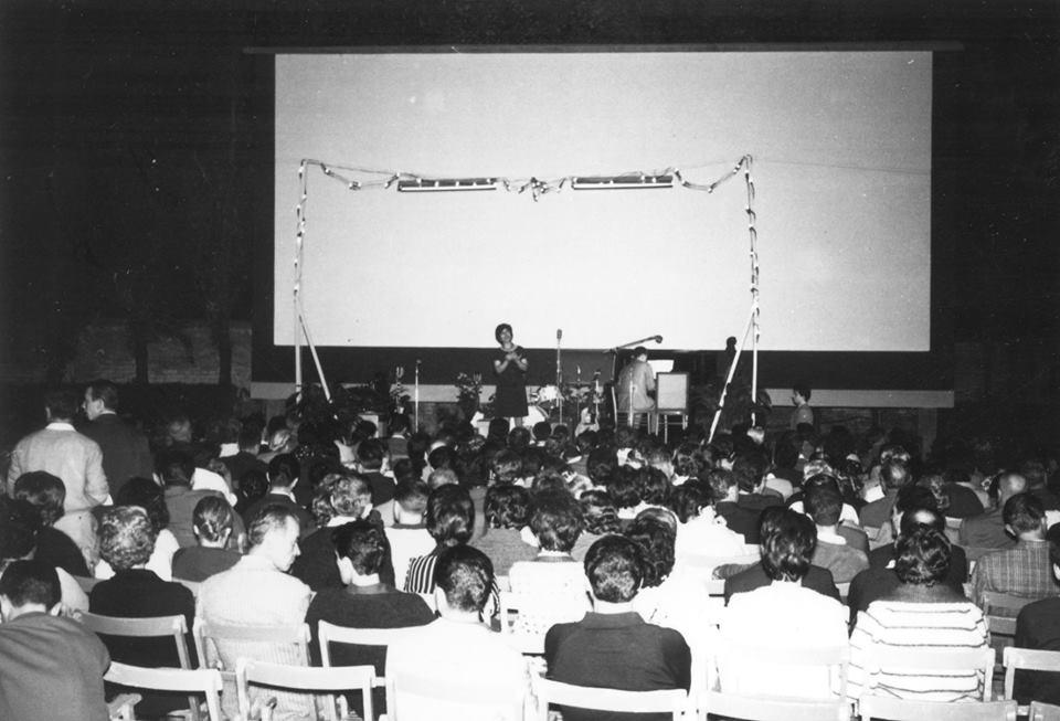 L'interno del cinema Aurora durante uno spettacolo musicale e l'esterno di via Pacinotti. (archivio Archenti)