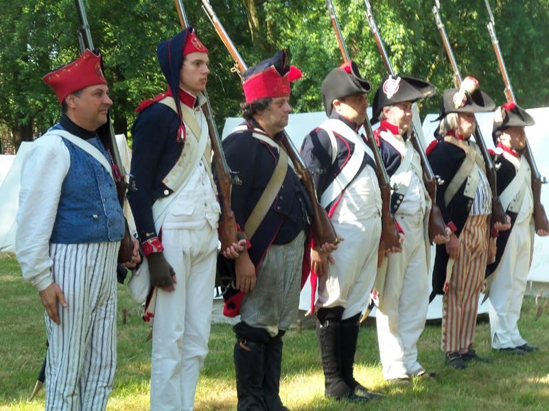 """59ÈME DEMI BRIGADE D'INFANTERIE DE LIGNE Spinetta Marengo (AL) - Periodo Napoleonico - Il gruppo storico ricrea un plotone di fanteria della 59° Demi Brigade d'Infanterie de Ligne del 1800, cioè una delle unità francesi che hanno combattuto a Marengo, e sotto tale """"bandiera"""" partecipano in giro per l'Italia e l'Europa alle manifestazioni di reenactement napoleonico, inquadrati spesso con molti altri gruppi """"fratelli"""" italiani, francesi, belgi, inglesi, tedeschi e maltesi. La loro sede è nella zona di Alessandria, a Spinetta Marengo. Come """"avversari"""" hanno di fronte gruppi austriaci (composti anche in parte da italiani, in particolare lombardi e veneti, cioè ex sudditi dell'impero austriaco), Piemontesi sabaudi, Cechi, Russi, Tedeschi ed Inglesi (e recentemente anche Svedesi e Spagnoli). Non sono né militaristi né fanatici, ma semplicemente appassionati della storia, in particolare di quella che ha visto l'esercito dei fanti-straccioni francesi percorrere sia le terre alessandrine che l'Europa intera, portando gli ideali della Rivoluzione del 1789 a tutte le popolazioni europee (nonché derubandole di tutto ciò che era possibile portare loro via). Come 59° Demi Brigade d''Infanterie de Ligne ricostruiscono di preferenza gli avvenimenti degli anni della prima e della seconda campagna d'Italia, ma non disdegnano partecipare anche ai fatti degli anni successivi, sino a Waterloo 1815. Come 59° si sono dotati di uno statuto, regolarmente registrato presso un notaio, con normali cariche sociali elette ogni due anni; """"militarmente"""" parlando, invece, sono tutti fanti (granatieri) di linea, più un sergente ed un sergente maggiore. Le armi sono perfettamente funzionanti, alcune originali, altre sono repliche attuali (sempre, naturalmente, """"sparanti"""")."""